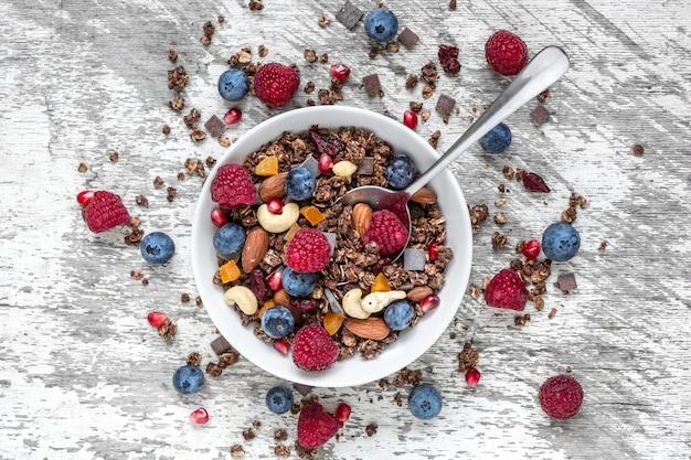 Muesli de chocolate caseiro ou granola em uma tigela com uma colher, frutas, frutos secos e nozes
