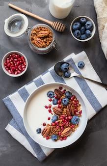 Muesli de granola caseiro com sementes de romã, mirtilo, noz-pecã e iogurte