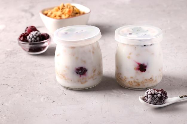 Muesli de granola crocante de mel com iogurte natural e frutas congeladas em potes de vidro fechados sobre fundo cinza