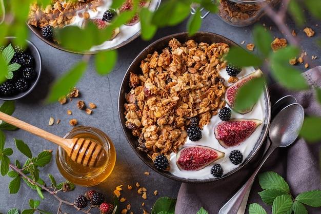Muesli de granola de aveia caseiro com iogurte e frutas vermelhas no café da manhã