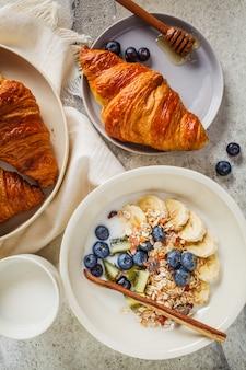 Muesli do café da manhã com frutas e croissants, fundo cinzento.