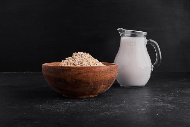 Muesli em uma tigela de madeira servido com uma jarra de leite.