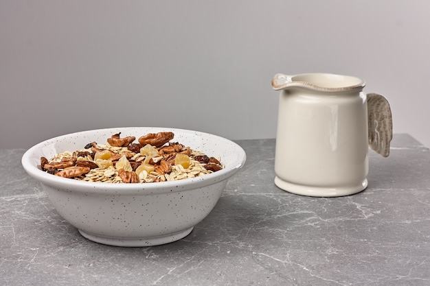 Muesli ou granola com frutas secas e nozes pecãs em uma tigela branca na mesa de pedra.