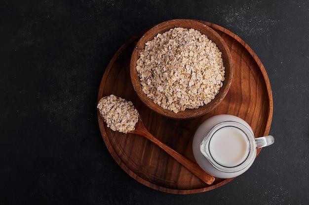 Mueslies em copos de madeira com uma jarra de leite em uma placa de madeira.