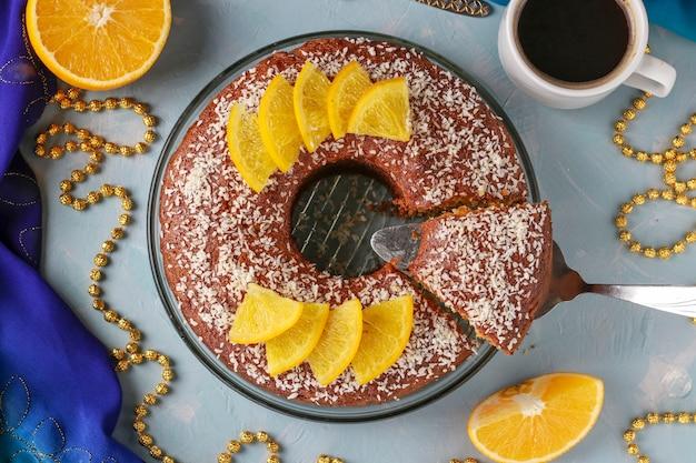 Muffin caseiro com laranjas com um furo no centro, polvilhado com flocos de coco em um fundo azul claro e uma xícara de café. vista superior