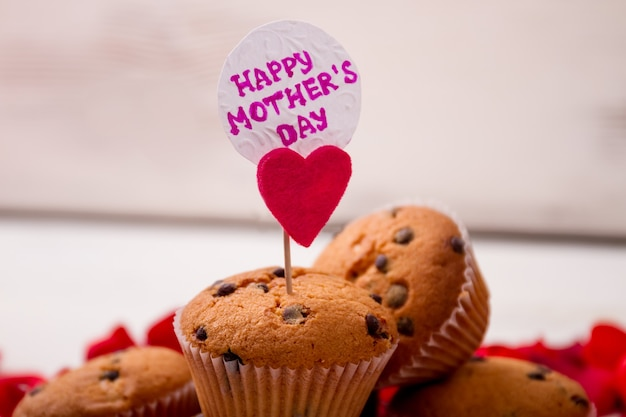Muffin com coração de cartão no palito de bolinho e sobremesa caseira de papel para a mãe
