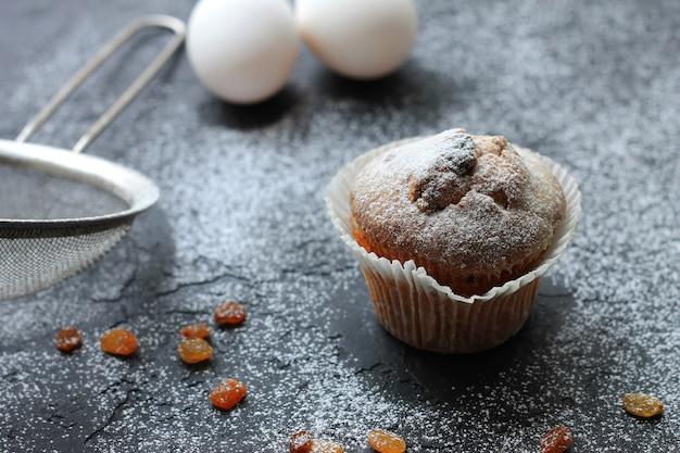 Muffin com passas polvilhadas com açúcar de confeiteiro sobre um fundo de madeira e são ingridient sobre um fundo desfocado