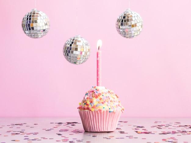 Muffin de aniversário delicioso com globos de discoteca