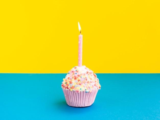 Muffin de aniversário delicioso com vela rosa