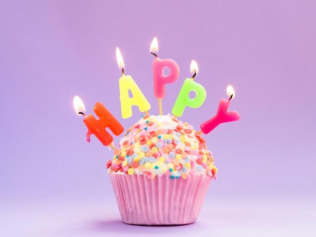 Muffin de aniversário delicioso com velas coloridas