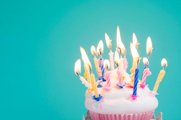 Muffin de aniversário gostoso com velas coloridas