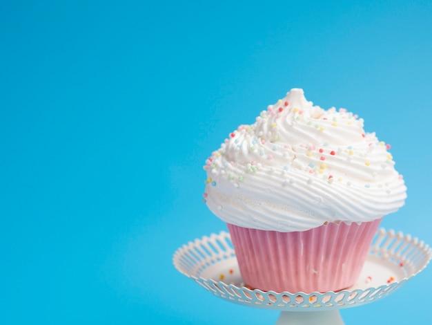 Muffin de aniversário gostoso sobre fundo azul