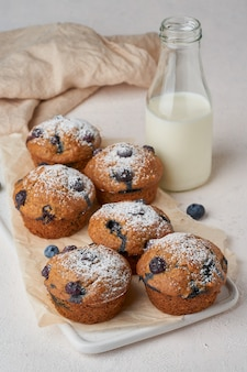 Muffin de blueberry, vista lateral, vertical. cupcakes com frutas na mesa de concreta branca, café da manhã