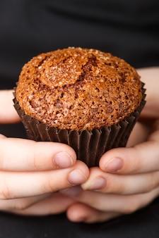 Muffin de chocolate caseiro com crosta de caramelo (açúcar) nas mãos das crianças