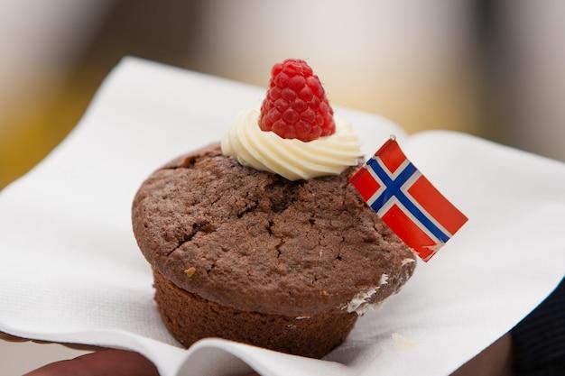 Muffin de chocolate com a bandeira norueguesa para a comemoração de 17 de maio