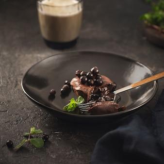 Muffin de chocolate com mirtilos em chapa preta sobre fundo escuro com café