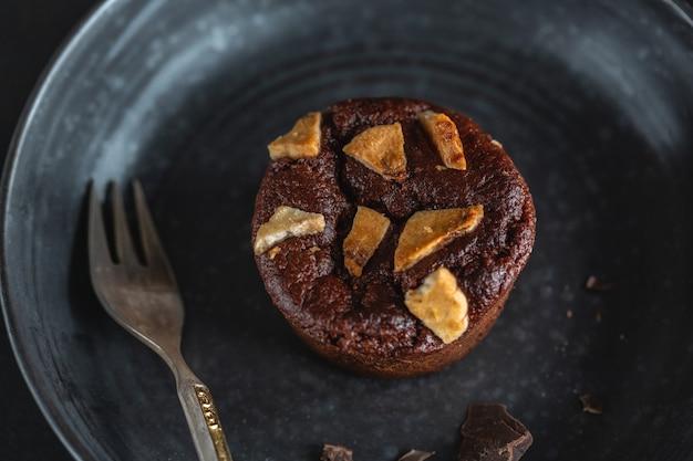 Muffin de chocolate com pedaços de banana no prato escuro com garfo