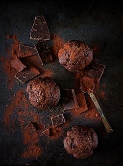 Muffin de chocolate no fundo escuro. vista do topo. lay plana