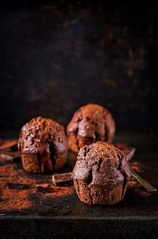 Muffin de chocolate no fundo escuro.