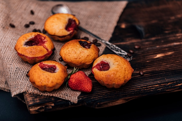 Muffin de morango e grãos de café em uma placa de madeira em uma mesa de madeira escura