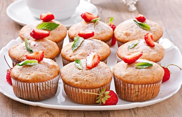 Muffin de morango em um prato branco com um morango fresco