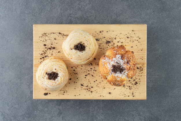 Muffin de nozes com pastéis e cacau em pó em uma tábua de madeira
