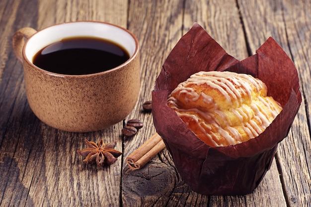 Muffin e xícara de café na mesa de madeira vintage