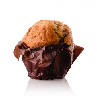 Muffin no papel marrom em um fundo isolado branco. bolo de esponja em uma superfície branca do espelho, close up.