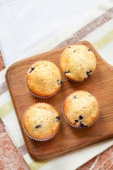 Muffins caseiros com mirtilos em uma placa de madeira