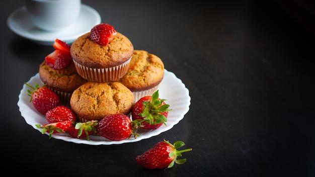 Muffins caseiros com morangos frescos na chapa branca na mesa preta.