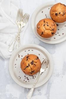 Muffins com chocolate no prato branco sobre fundo de cerâmica