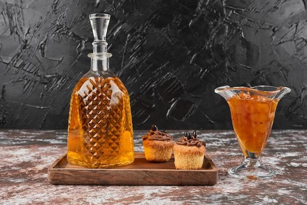 Muffins com confiture e bebida numa placa de madeira.