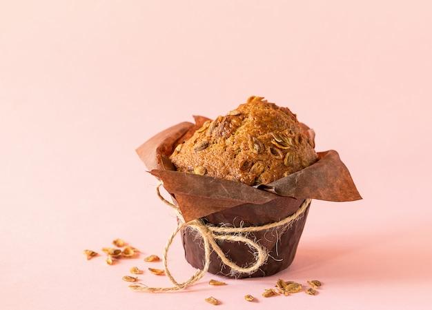 Muffins com flocos de trigo em close-up de embalagem de papel marrom no fundo rosa. sobremesa saudável vegan.
