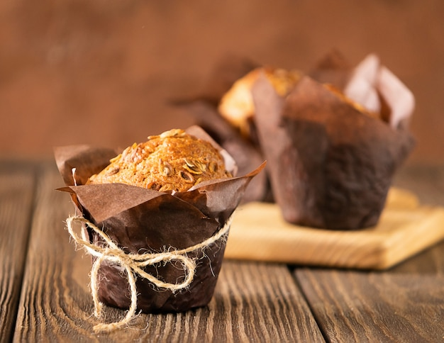 Muffins com flocos de trigo em papel marrom fundo de madeira close-up de embalagem.