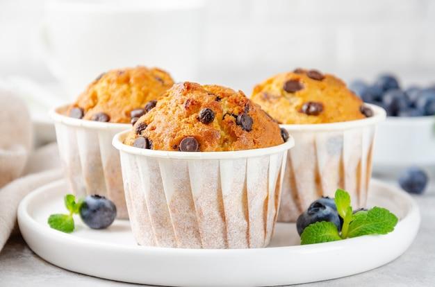 Muffins com gotas de chocolate em um prato branco com uma xícara de café e mirtilos frescos em um fundo cinza de concreto. copie o espaço.