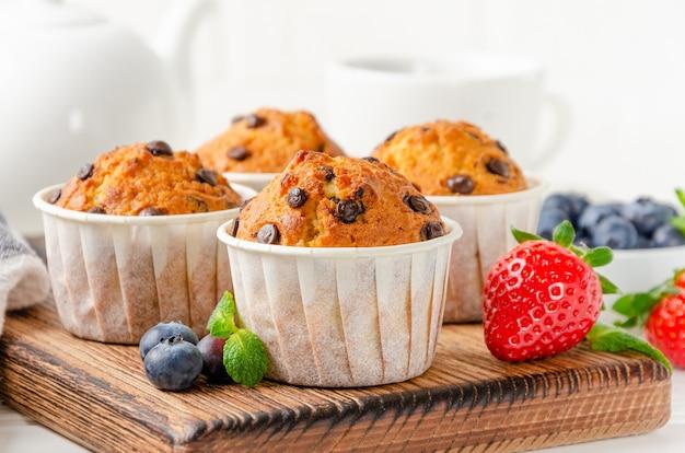 Muffins com gotas de chocolate em uma borda de madeira em um fundo branco com frutas frescas. copie o espaço.