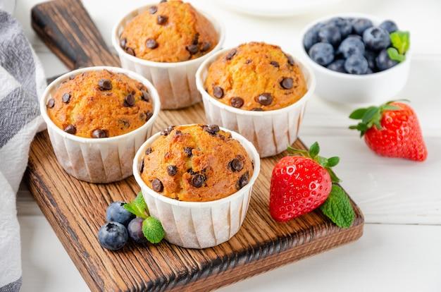 Muffins com gotas de chocolate em uma borda de madeira em um fundo branco com frutas frescas.