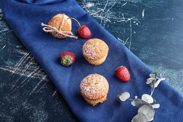 Muffins com morangos em uma toalha azul.