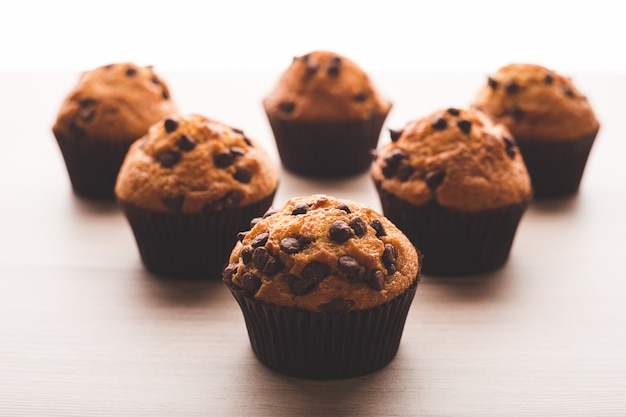 Muffins com um fundo branco em uma mesa de madeira
