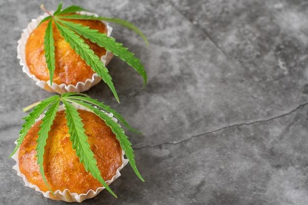 Muffins cupcake de cannabis e folhas em fundo cinza escuro