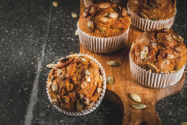 Muffins de abóbora com especiarias tradicionais de outono na mesa de corte de madeira