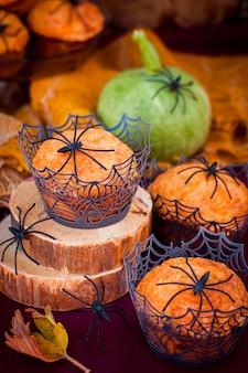 Muffins de abóbora de halloween decorados com aranhas e teia de aranha