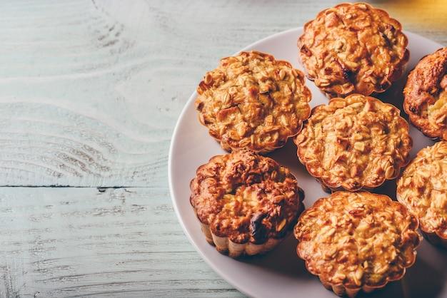 Muffins de aveia cozida em prato branco sobre madeira clara