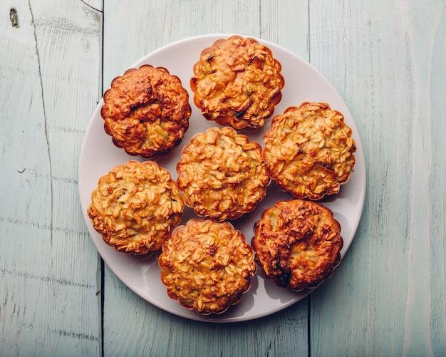 Muffins de aveia cozida em um prato branco sobre uma mesa de madeira clara