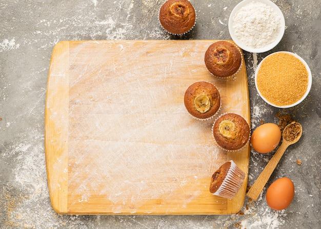 Muffins de banana caseiros e ingredientes de cozinha são dispostos em uma tábua de madeira.