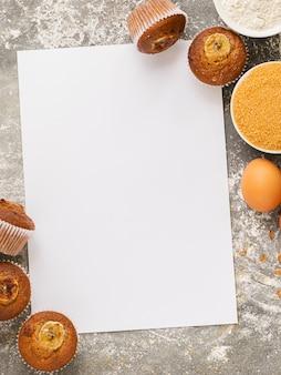 Muffins de banana caseiros e ingredientes para cozinhar são dispostos em uma folha em branco branca. sobremesa saudável vegan.