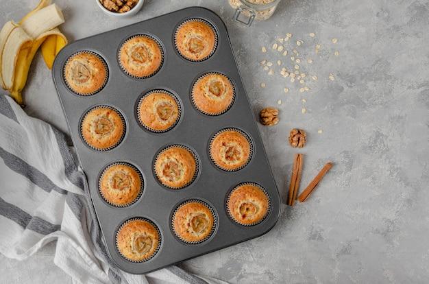 Muffins de banana com aveia, nozes e canela em forma de cozimento no fundo cinza de concreto.