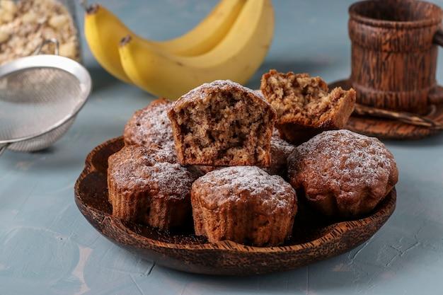 Muffins de banana com flocos de aveia polvilhados com açúcar de confeiteiro em um prato de coco