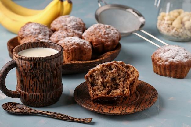 Muffins de banana com flocos de aveia polvilhados com açúcar em um prato de coco e um copo de leite