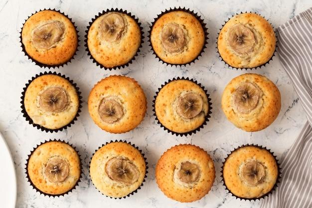Muffins de banana em uma mesa branca. bolinhos doces com uma fatia de fruta. vista plana, vista superior